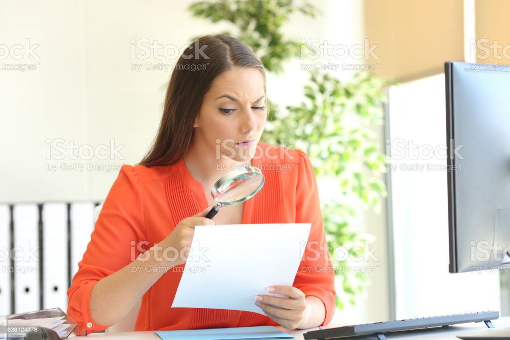 Businesswoman examining a contract meticulously stock photo