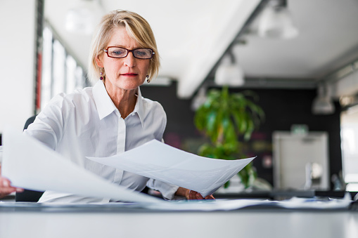 A photo of mature businesswoman examining documents at desk. Concentrated professional is analysing papers in office. Executive is in formals.