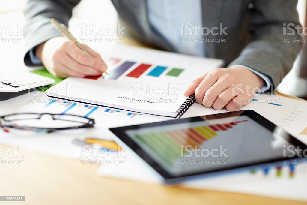 Businesswoman examining financial graph at desk in office stock photo
