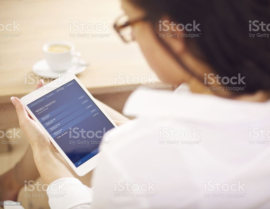 Businesswoman Examining Her Bank Account on Digital Tablet stock photo