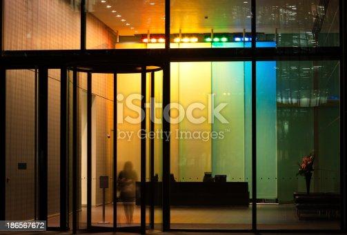 istock Businesswoman Exiting Illuminated Lobby Through Revolving Door 186567672