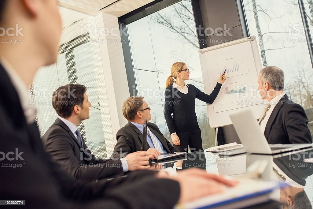 Businesswoman explaining and pointing to a graph chart stock photo