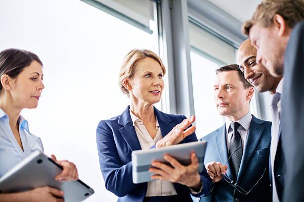 businesswoman explaining new business ideas to colleagues - senior business woman tablet imagens e fotografias de stock