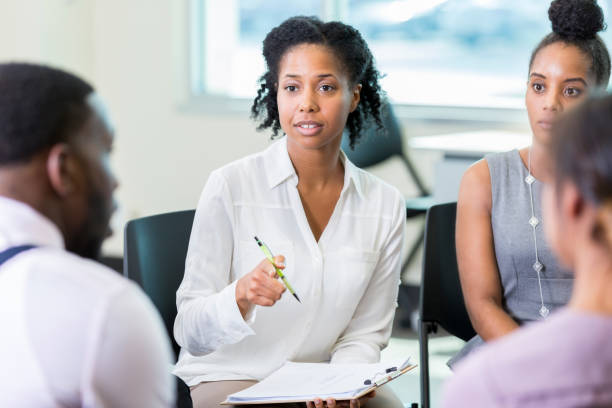 businesswoman facilitates meeting - school counselor stock photos and pictures