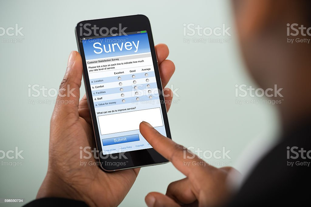 Businesswoman Filling Online Survey On Mobile Phone stock photo