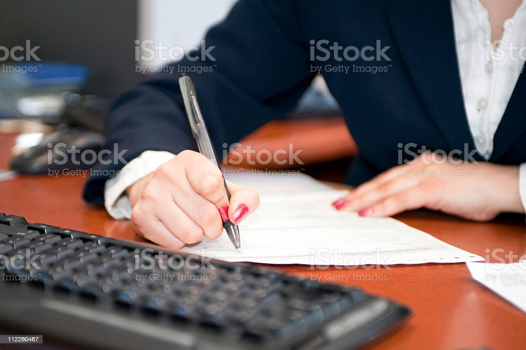 Businesswoman filling out contract stock photo