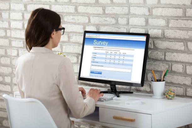 businesswoman filling survey form on computer - perito foto e immagini stock