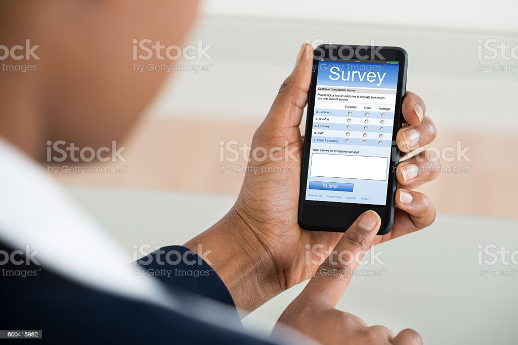 Businesswoman Filling Survey Form On Mobile Phone stock photo