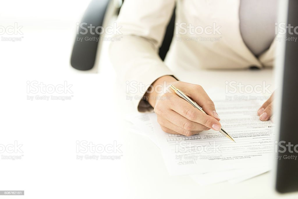 Businesswoman filling tax form stock photo