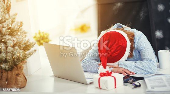 istock businesswoman freelancer tired, asleep working at computer at Christmas 873875596