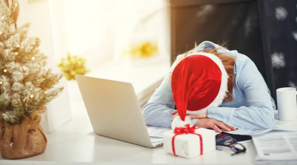 businesswoman freelancer tired, asleep working at computer at christmas - christmas background стоковые фото и изображения