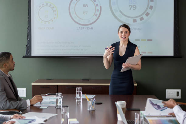 Businesswoman gestures during presentation stock photo