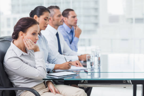 Businesswoman getting bored while attending presentation stock photo