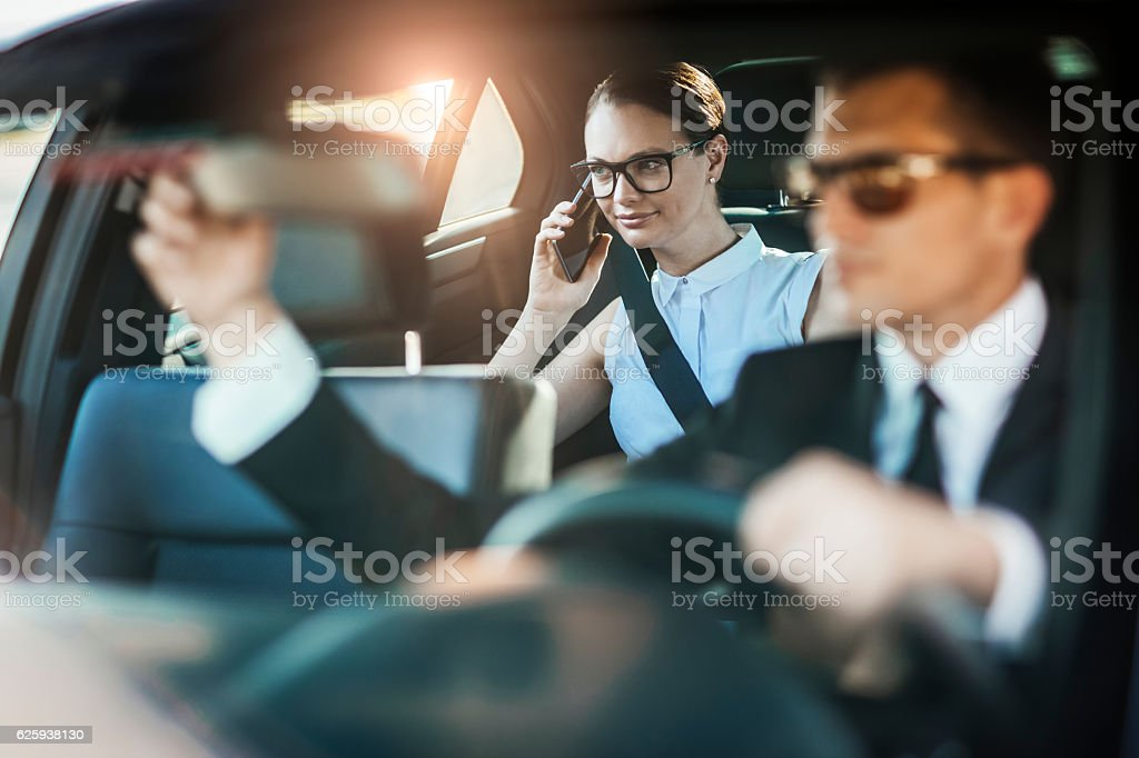Businesswoman getting chauffeured stock photo