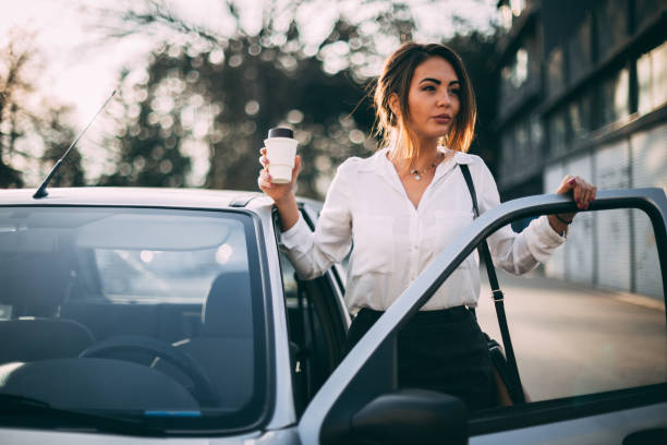 Businesswoman getting coffee in the morning and entering car stock photo