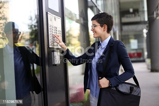 Young businesswoman on the street, getting into a building. About 20 years old, Caucasian female.