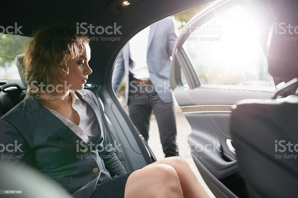 Businesswoman getting out of a car stock photo