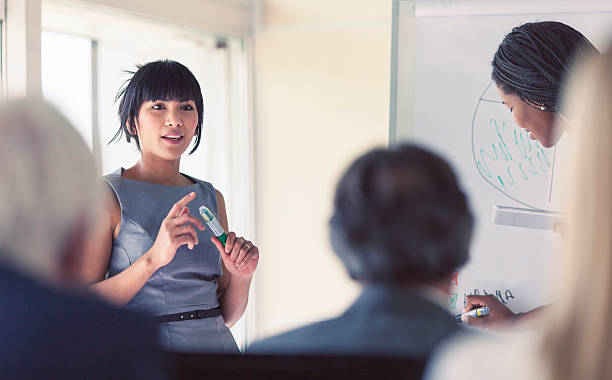 Businesswoman giving a presentation Young businesswoman giving a presentation staff meeting stock pictures, royalty-free photos & images