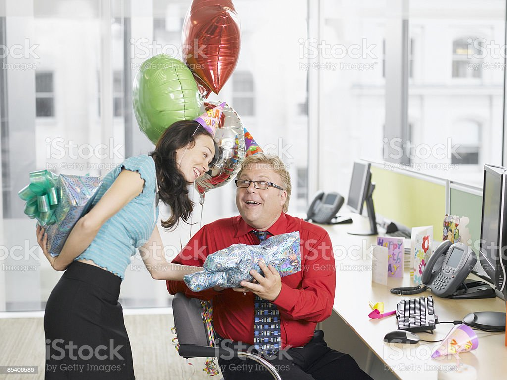 Businesswoman giving birthday gift to co-worker royalty-free stock photo