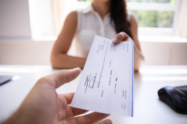 Businesswoman Giving Cheque To Colleague stock photo