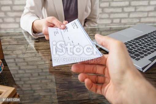 istock Businesswoman Giving Cheque To Her Colleague 915451034