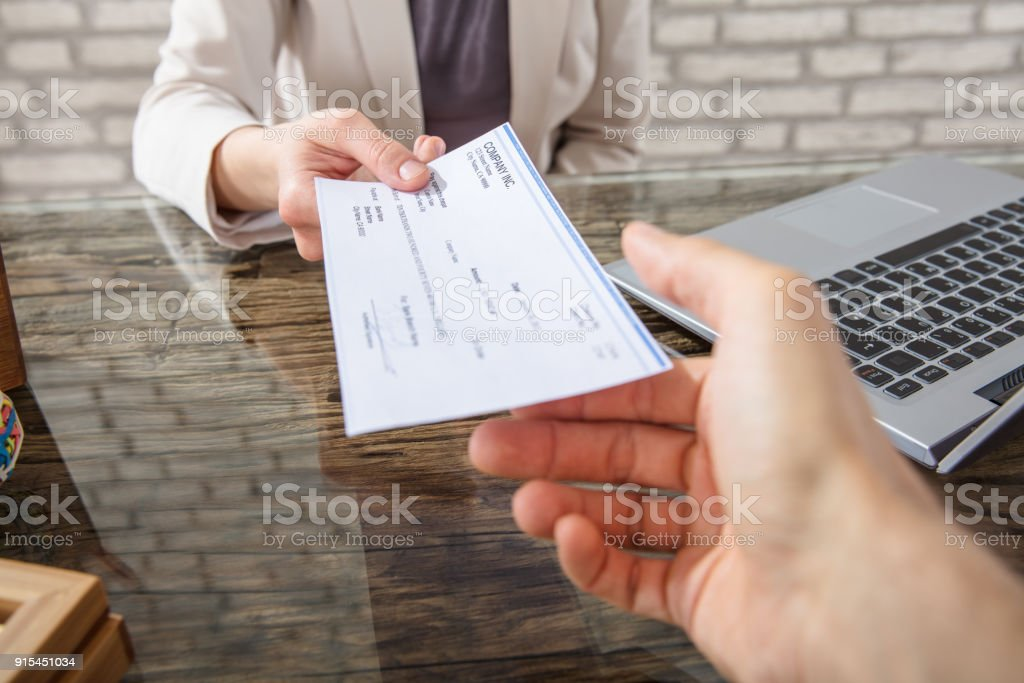 Businesswoman Giving Cheque To Her Colleague stock photo