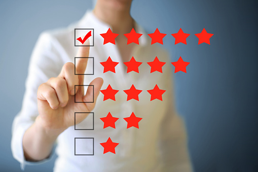 Businesswoman using touch screen to give five star review.