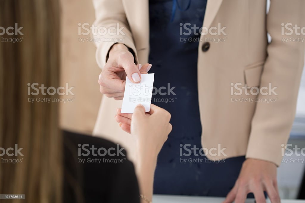 Businesswoman giving her businesscard to her partner stock photo