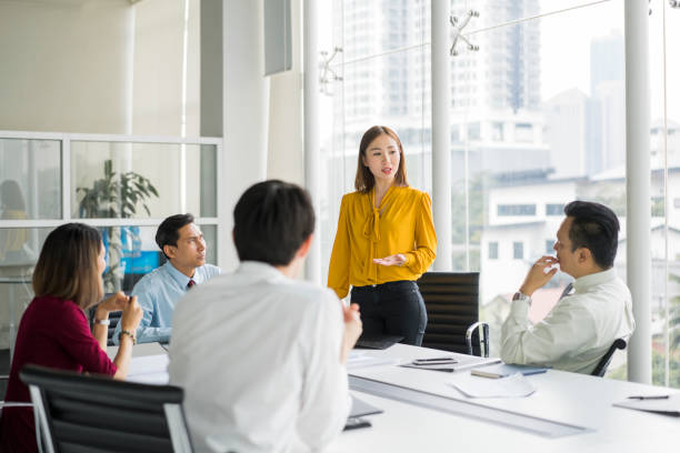 Businesswoman giving presentation in board room Confident businesswoman giving presentation in board room. Professionals are in meeting at conference table. They are sharing ideas in office. business Malaysia stock pictures, royalty-free photos & images