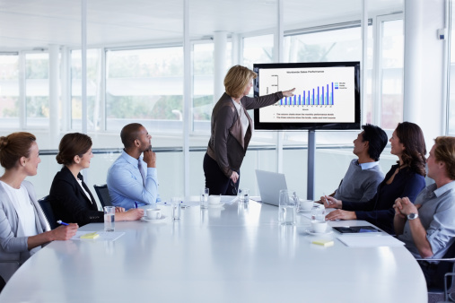Businesswoman giving presentation to colleagues in conference meeting