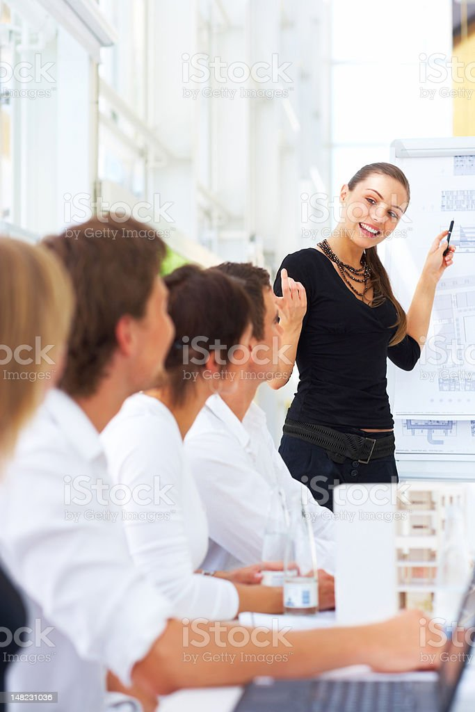 Businesswoman giving presentation to her colleagues royalty-free stock photo
