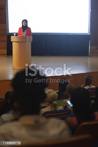 1133973551 istock photo Businesswoman giving speech in front of audience in the auditorium 1133855115