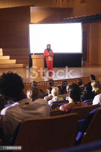 1133973551 istock photo Businesswoman giving speech in front of audience in the auditorium 1133855349