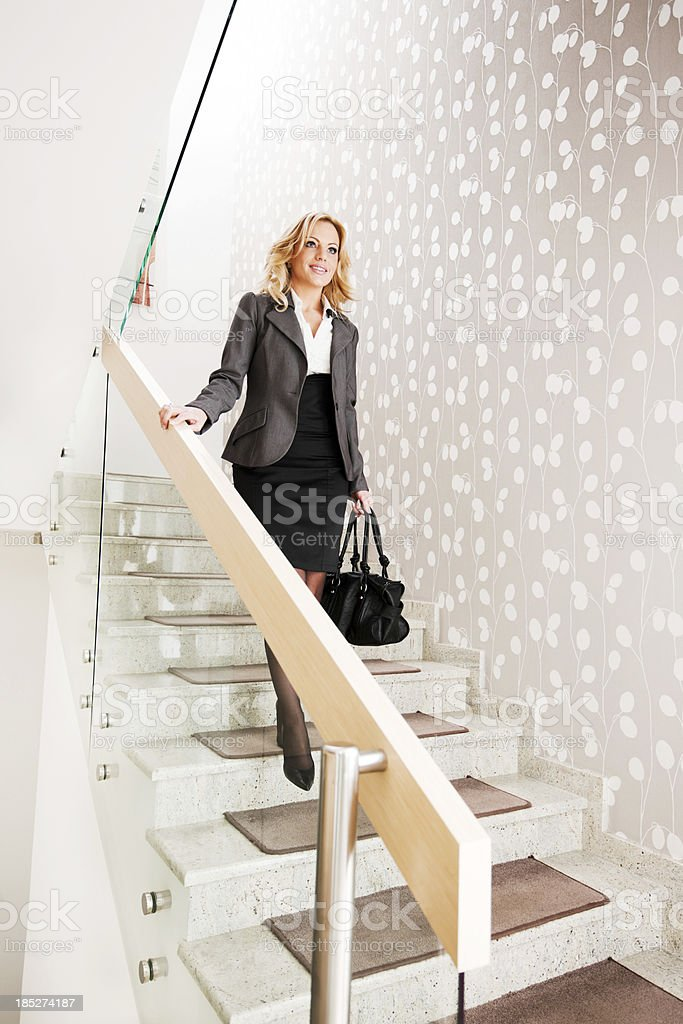 Businesswoman going down the stairs. stock photo
