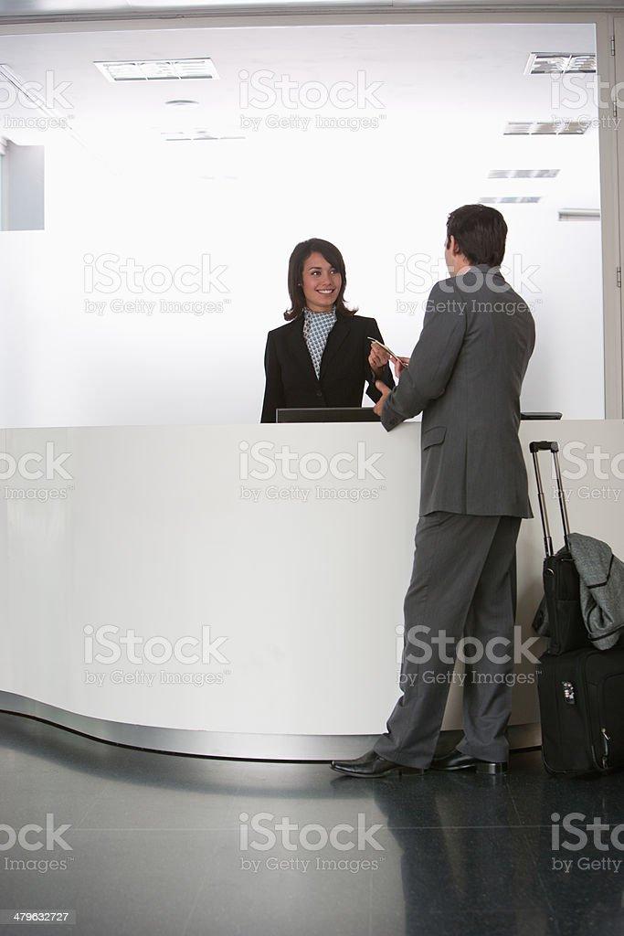 Businesswoman greeting businessman at reception desk stock photo