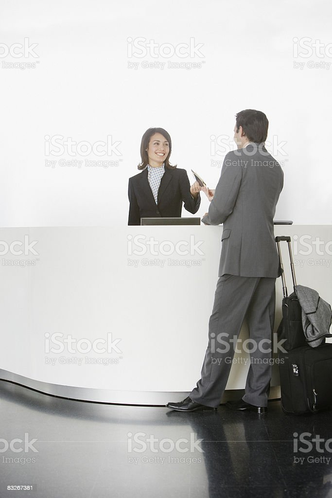 Businesswoman greeting businessman at reception desk royalty-free stock photo