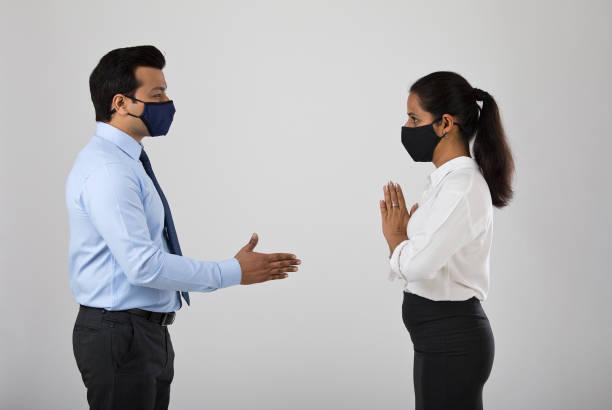 Geschäftsfrau begrüßt Geschäftsmann mit Namaste statt Handschlag, um die Ausbreitung von Virus-Infektionskrankheit zu verhindern – Foto