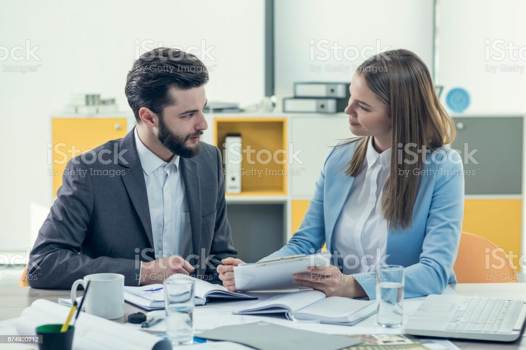 Businesswoman guiding man with paperwork royalty-free stock photo