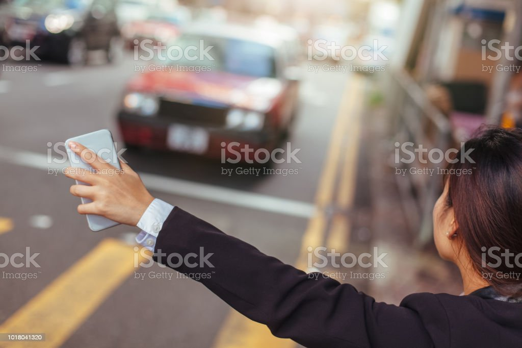 Geschäftsfrau hagelt Taxi in die Stadt – Foto
