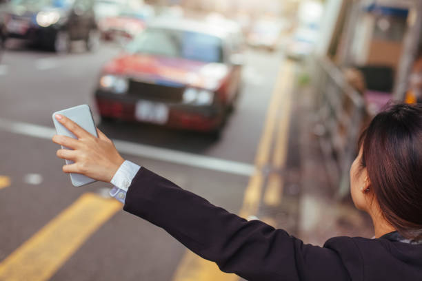 Businesswoman hailing taxi in city stock photo