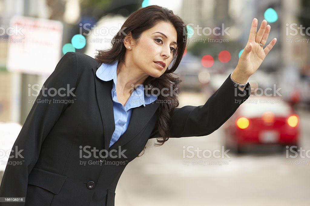 Businesswoman Hailing Taxi In Street stock photo