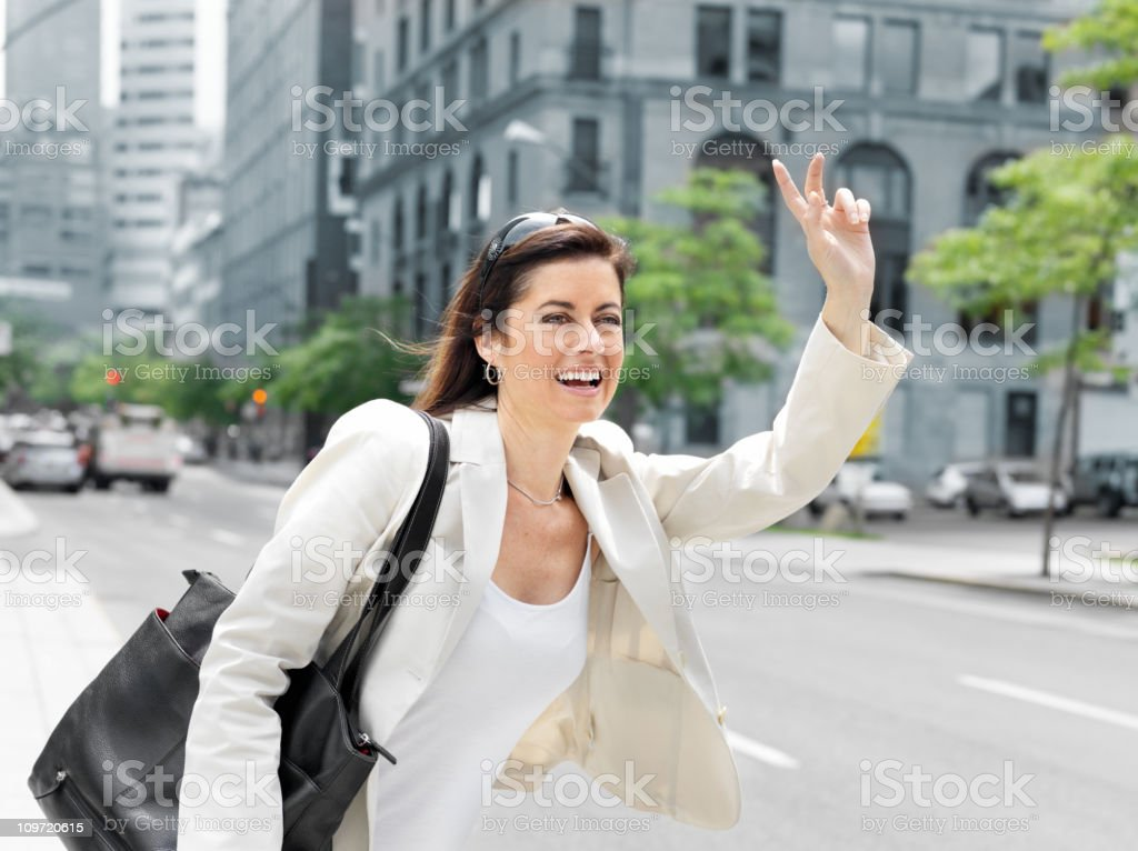 Businesswoman hailing taxi royalty-free stock photo