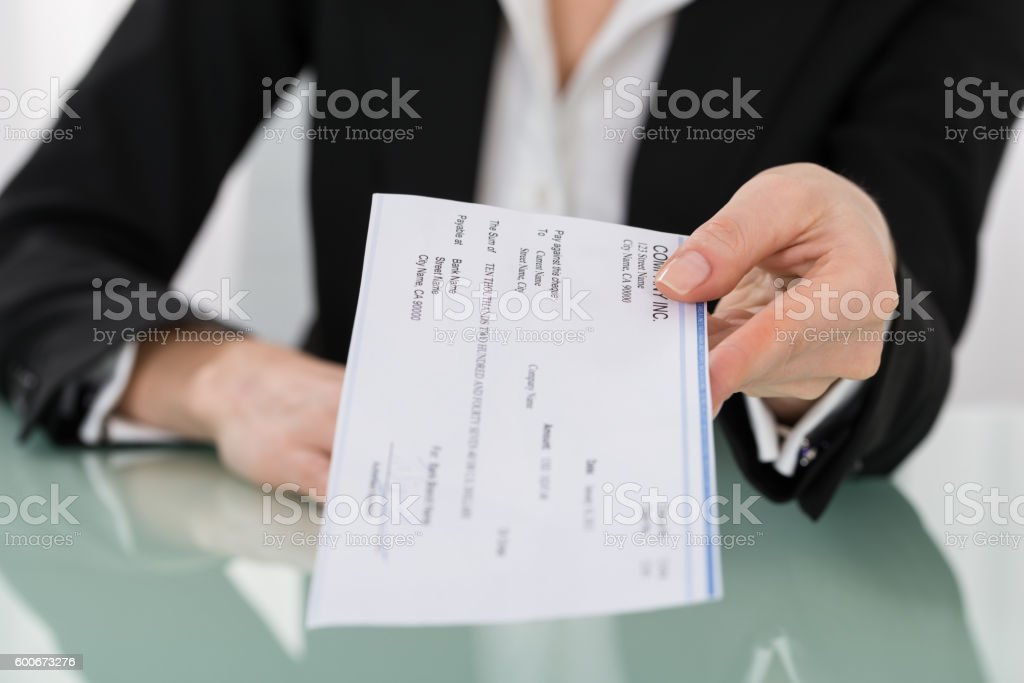 Businesswoman Hand Giving Cheque stock photo