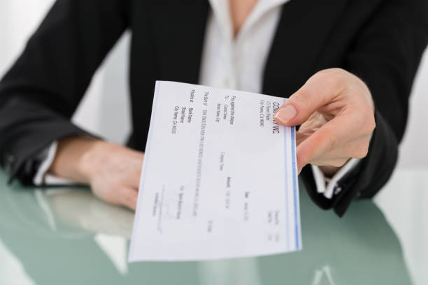 businesswoman hand giving cheque - wages stock photos and pictures