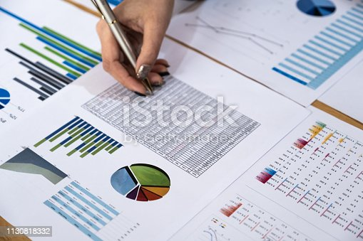 istock Businesswoman hand holding pen and pointing at financial paperwork in co-working space. 1130818332