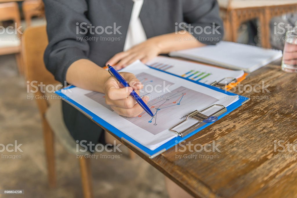 Businesswoman hand holding pen while dealing with diagram report stock photo
