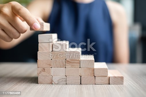 Businesswoman hand placing or pulling wooden block on the building. Business planning, Risk Management, Solution and strategy Concepts