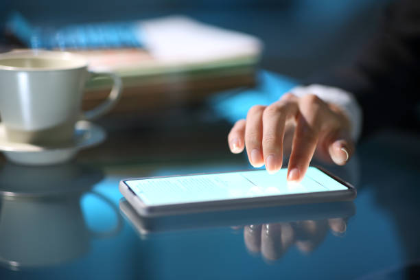 Businesswoman hand signing online on smart phone in the night stock photo