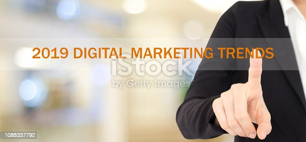 istock Businesswoman hand touching 2019 digital marketing trends over blur office background, banner, 2019 business and technology concept 1088337792