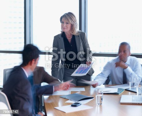 1163429625istockphoto Businesswoman handing papers to three businesspeople in a boardroom 79365742